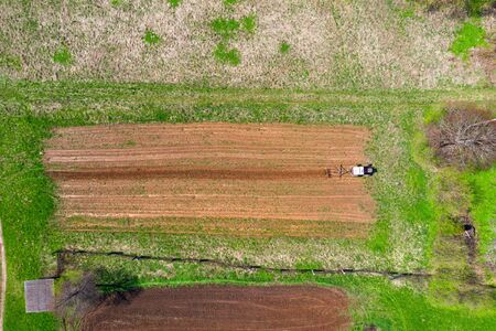 Tractor plows a small field in the village before planting vegetables. Aerial height view