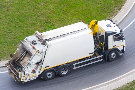 Large garbage truck to transport household waste travels along the city highway, aerial view