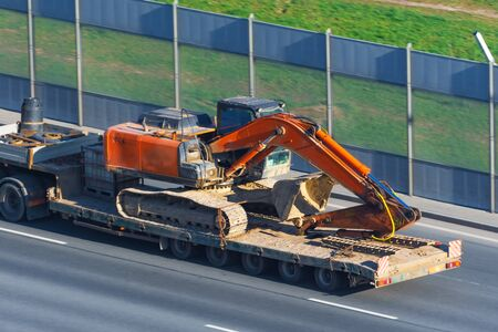 Heavy excavator on transportation truck with long trailer platform on the highway in the city