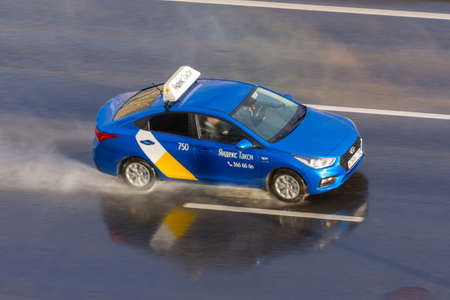 Blue passenger car Yandex Taxi rides on the wet rain spray highway aerial view. Russia, Saint-Petersburg. 15 may 2020
