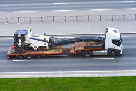 Transportation of equipment for cutting and removing old asphalt pavement for road repair on a truck platform of a truck trailer on a highway in a city, side aerial view Stock Photo