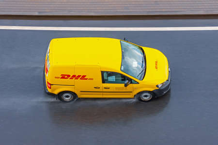 DHL world wide courier company delivery small cargo car on the highway city. Russia, Saint-Petersburg 15 may 2020