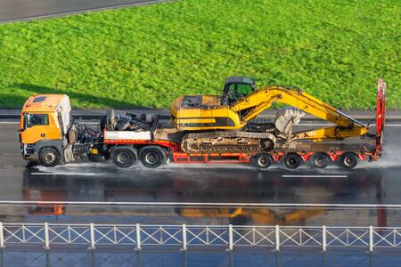 Heavy yellow excavator on transportation truck with long trailer platform on the highway wet asphalt after rain in the city