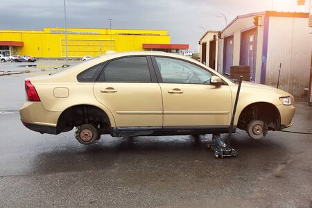 Replacing tires on wheels, a car without a wheels on a jack, express service maintenance, side view