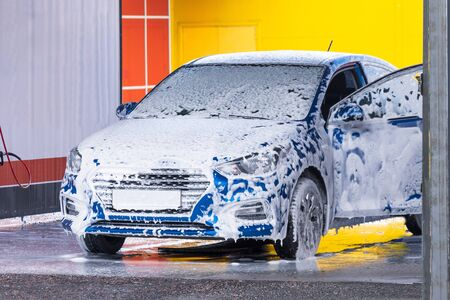 Car wash with open door covered in white foam