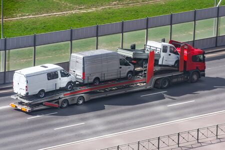 Heavy truck with trailer platform tow for transporting mini buses on the city highway Stok Fotoğraf