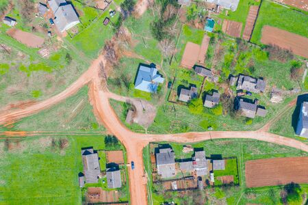 Aerial view from the height of the rural village with houses and streets, plowed fields, meadows in the summer