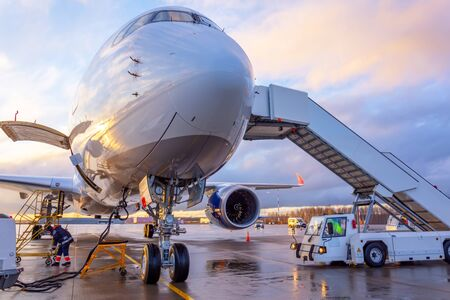 Nose view of an airplane with gangway for boarding parked at an airport during sunset bright light shine and clouds in the sky