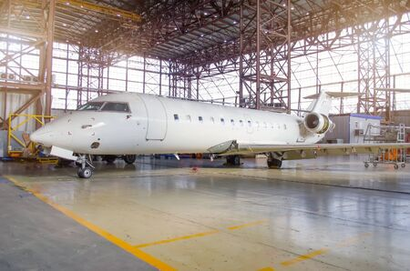 White aircraft in the hangar on a large-scale inspection, repair 免版税图像
