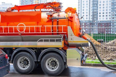 Pumping water from sewage canals during the construction of roads in the city. Truck with orange water tank