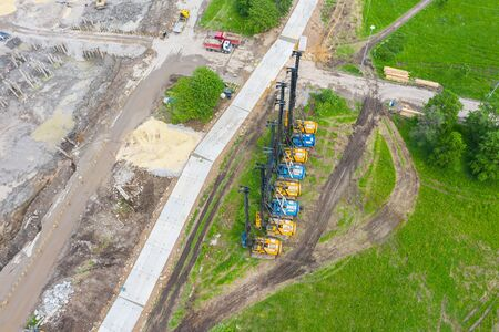 Equipment for installing piles in the ground, heavy machines for driving foundation pillars are lined up. Construction aerial view from a height