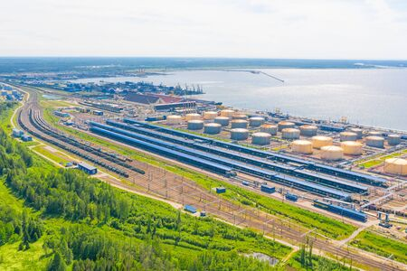 Huge port with oil tanks for storing liquid fuel on the seashore factory, far away port with bulk cargo - coal, ore, minerals