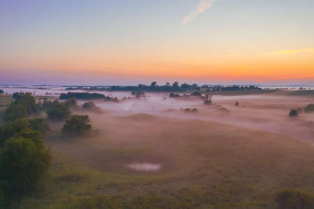 Evening foggy landscape aerial view after rain in a valley of a lake and swamp among meadows and forests Stock Photo - 150663193