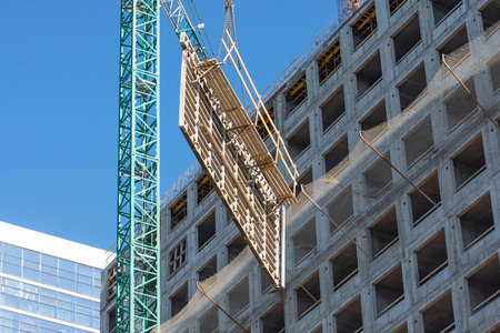 Construction of a building, crane lifts reinforcement for floors and walls of a multi-storey building Stock Photo - 150643499