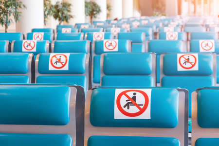 Rows of turquoise colored seats in the waiting room with a sign applied- do not occupy, do not sit down. Social distance concept, pandemic precautions. 版權商用圖片