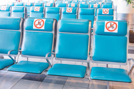 Rows of turquoise colored seats in the waiting room with a sign applied- do not occupy, do not sit down. Social distance concept, pandemic precautions.