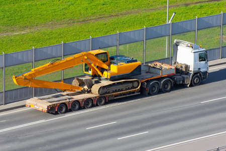 Heavy new yellow excavator long boom bucket on transportation truck with long trailer platform on the highway in the city