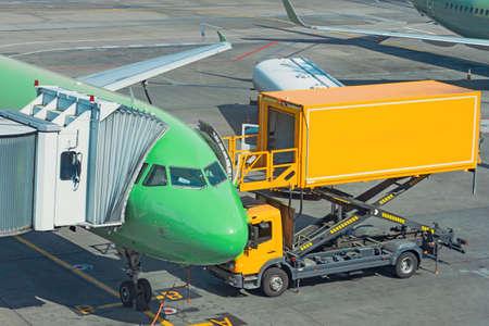 Yellow truck next to a passenger plane, pre flight service airport