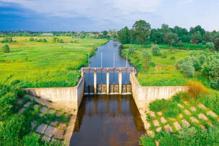 Dense on a small river, view of the floodgates. River among fields and meadows, aerial view