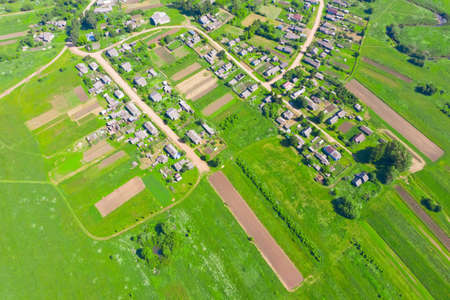 Aerial view from the heights of a countryside village with fields of vegetable crops