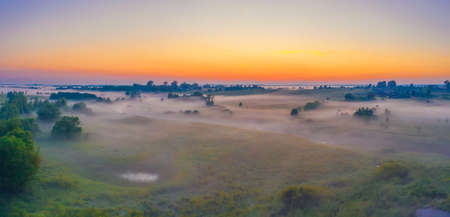Panorama of a summer wet meadow after a rain with swamps along the river during sunset