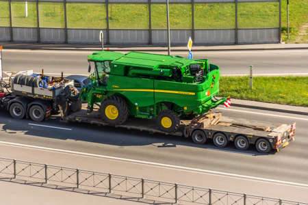 Transportation of harvester John Deere S760i loaded onto cargo platformon highway in the city. Russia, Saint-Petersburg. 22 may 2020