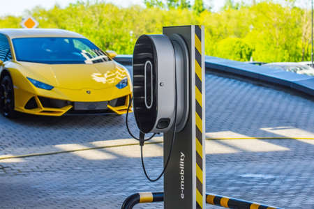 Supercar Lamborghini Aventador yellow color parked to the electric station power supply e-mobile. Russia, Saint-Petersburg. 01 June 2020