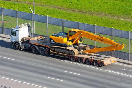Excavator Hyundai robex 220 LC-95 Truck trailer loaded onto cargo platformon city highway. Russia, Saint-Petersburg. 19 may 2020
