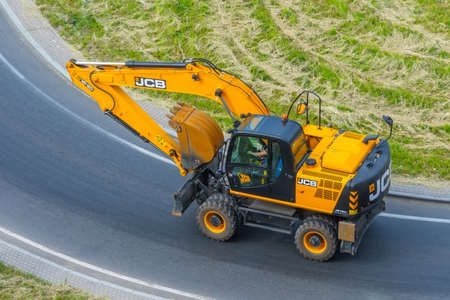 Excavator yellow JCB JS160W ride on the road to turning. Russia, Saint-Petersburg. 16 june 2020