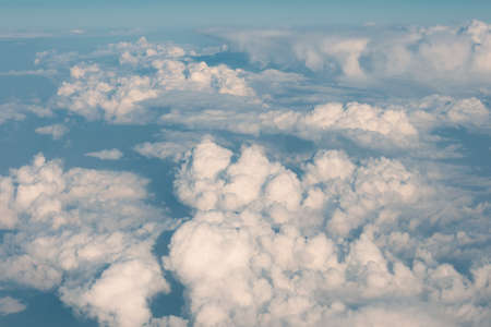 Dense cumulus clouds cover the sky as seen from flight altitude