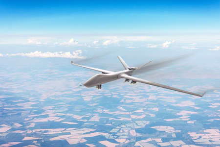 Unmanned military aircraft flies high in the sky at high speed over fields, blue sky clouds