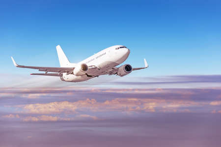Evening sky with dense clouds and a passenger plane flying high at speed Stock Photo