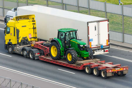 Transportation of agricultural tractor John Deere 6175m loaded onto cargo platformon highway in the city. Russia, Saint-Petersburg. 15 june 2020