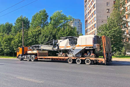 Transportation of equipment for cutting and removing old asphalt pavement for road repair truck platform of a truck trailer on highway in a city