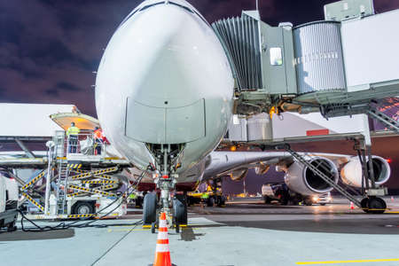A huge plane parked next to the passenger terminal at midnight before the departure of the flight Stock Photo