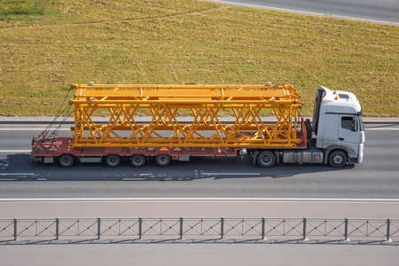 Transportation of tower crane components on pltaform truck trailers along the highway