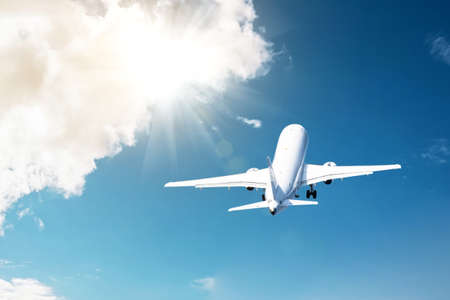 Civil plane took off into the blue sky and flies away into the bright rays shine the sun in the clouds
