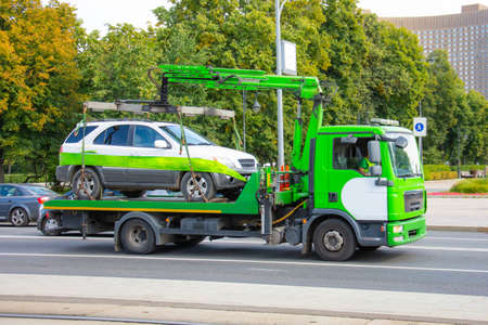 Towing of vehicle on forklift truck. Tow truck with equipped suspension mechanism crane evacuation and transportation to a fine parking lot