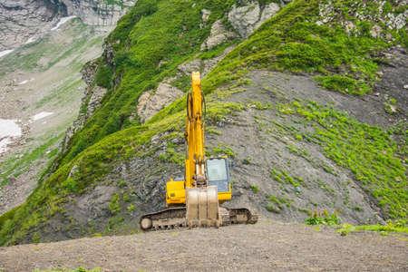 Excavator heavy equipment in mountains on steep range slopes