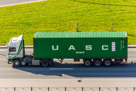 Truck with trailer and green container company UASC on city highway. Russia, Saint-Petersburg. 25 august 2020