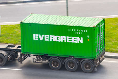 Truck with trailer and green container company Evergreen on city highway. Russia, Saint-Petersburg. 01 august 2020