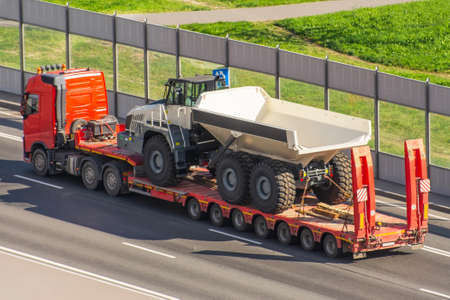 Transportation of a huge truck for mining on the trailer platform Stock Photo