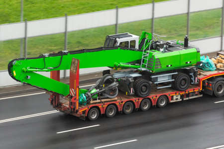 Heavy new green technics long boom claws for gripping scrap metal on transportation truck with rubber wheels long trailer platform on the highway