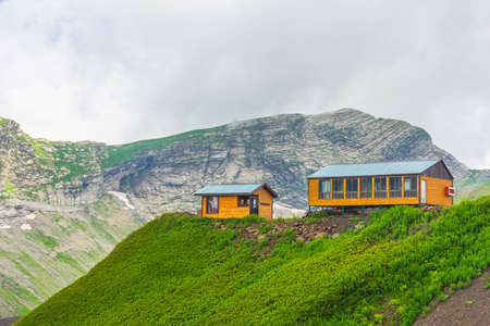 Two wooden houses on top of a mountain