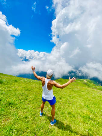The guy on the top of the mountain ridge among the meadows looks in surprise at the sky with his hands up, in the distance the blue sky and white clouds