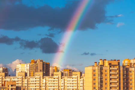 Rainbow in the sky after rain over multi-story houses residential area of the city