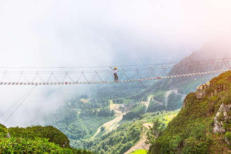 View of the mountain landscape gorge, tourist human walking along an extreme staircase over a precipice Stock Photo