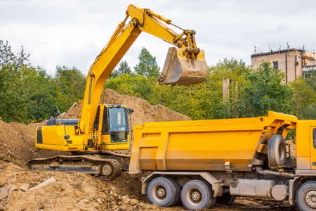 Yellow truck and excavator load soil with sand during road construction in urban area Stock Photo