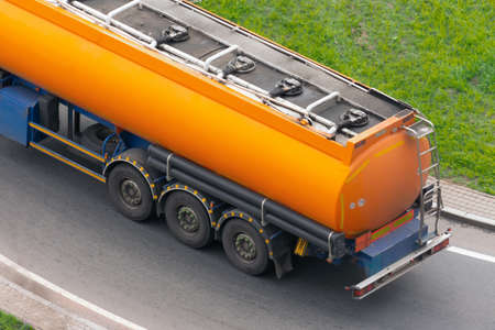 Large orange tank trailer tanker truck rolling on highway