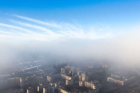 The city is under a layer of fog and low clouds, from above there is a clear blue sky